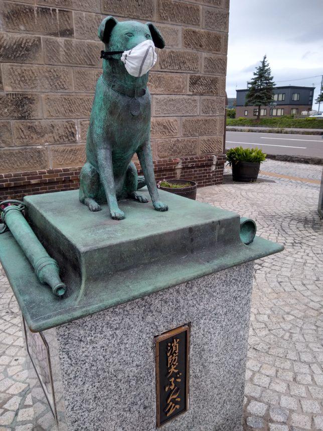 コロナ禍の象徴とも感じる犬の銅像にマスク
